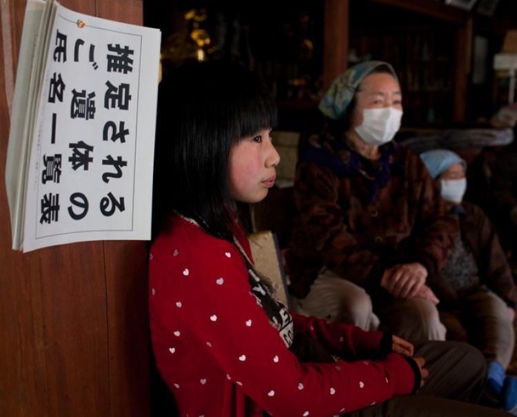 A list of names of earthquake and tsunami victims hangs on a wall as Japanese refugees wait for aid at a Buddist temple used as an evacuation centre in Ofunato, Iwate prefecture on April 4, 2011.  (Yasuyoshi Chiba/Getty Images)
