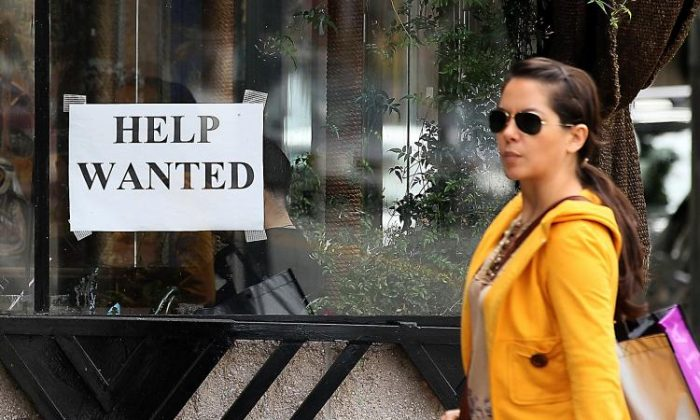 A pedestrian walks by a help wanted sign in San Francisco, California, on March 25, 2011. (Justin Sullivan/Getty Images)