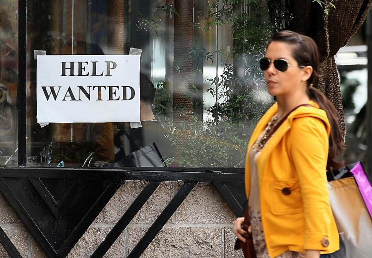 SAN FRANCISCO, CA - MARCH 25: A pedestrian walks by a help wanted sign. A report by the California Economic Development Department shows that California's unemployment rate dropped to 12.2% in February, down from 12.4% in January after the state added 100,000 new jobs. California has the second highest jobless rate in the nation. (Justin Sullivan/Getty Images)