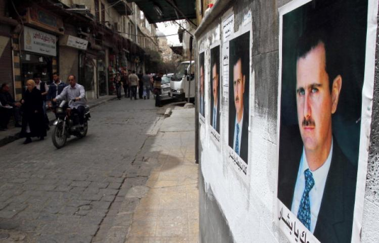 Posters of Syrian President Bashar al-Assad decorate a street as Syrians walk in the old city of Damascus on April 2, 2011. (Anwar Amro/AFP/Getty Images)
