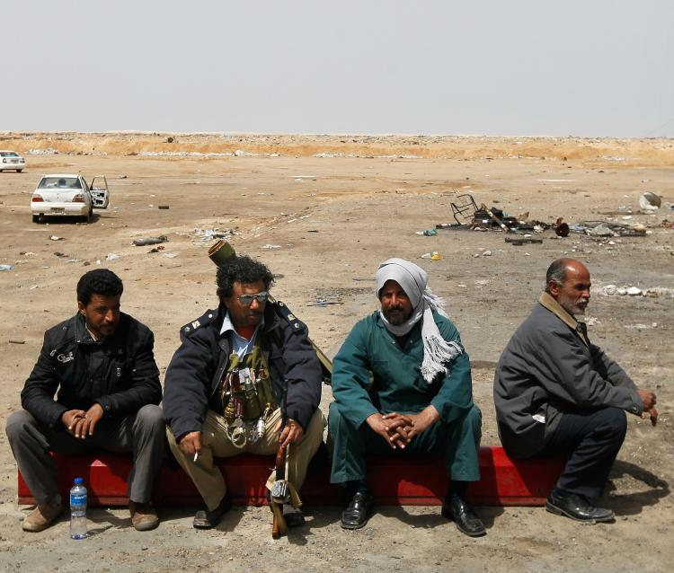 TOUGH SPOT: Libyan rebel soldiers sit at a checkpoint on a road leading to front-line positions April 6 near Brega, Libya. While the war against Libyan leader Moammar Gadhafi is still being waged, the task of nation-building, when it's over, may keep the U.S. and NATO in the country for even longer. (Chris Hondros/Getty Images)
