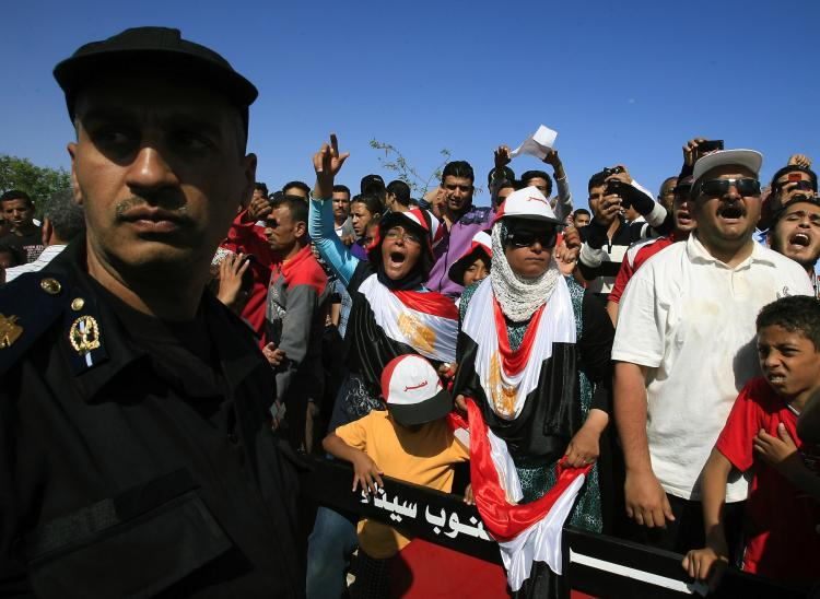 An Egyptian policeman stands guard as protesters shout slogans against ousted President Hosni Mubarak outside the Sharm el-Sheikh International Hospital in the resort town on April 13. Mubarak was admitted to intensive care after he reportedly suffered a heart attack during questioning by prosecutors.  (AFP/Getty Images)