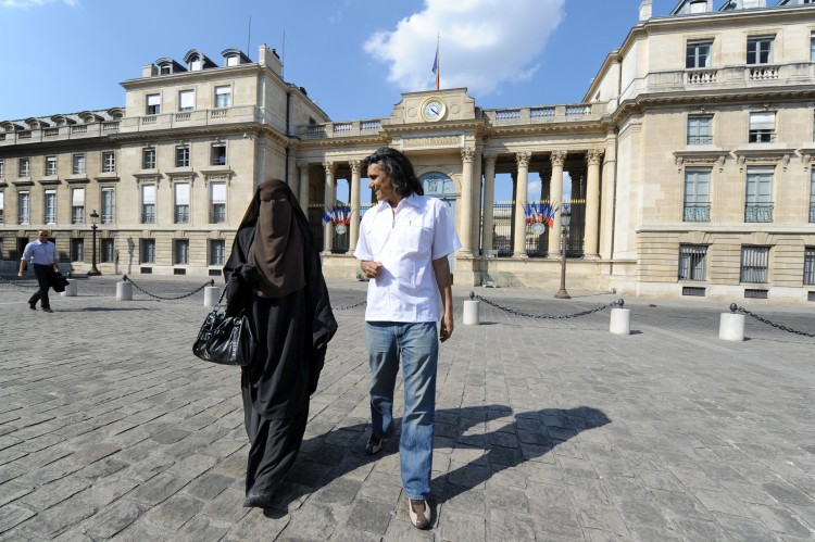 A woman wearing a niqab (L) and real estate magnate Rachid Nekkaz (R) walk in front of the French National Assembly during a symbolic protest against France's ban on wearing full-face veils in public, April 20 in Paris. (Mehdi Fedouach/AFP/Getty Images)