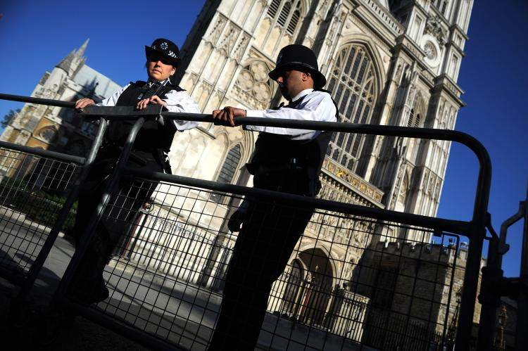 Police officers stand guard in the grounds of Westminster Abbey in London on April 27. To prevent any protests from forming, authorities are closely watching Facebook and Twitter for any signs of event planning. (Dimitar Dilkoff/AFP/Getty Images)
