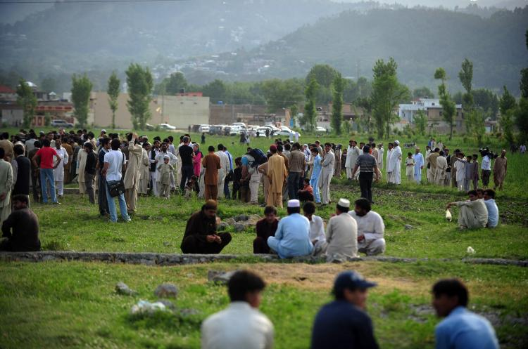 Pakistani people and media personnel gather in front of the final hiding place of Al-Qaeda chief Osama bin Laden in Abbottabad on May 5. Pakistan faces the prospect of Osama bin Laden's final hiding place becoming a shrine or macabre tourist spot unless the military destroys a compound attracting hundreds of visitors a day. (Asif Hassan/Getty Images)