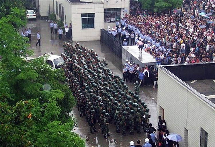 Chinese riot police in formation at the gate around the Lichuan City compound, as thousands  of people gather outside, on June 9 in Hubei Province. The crowd would clash with police and tear down the gate. (AFP/Getty Images)