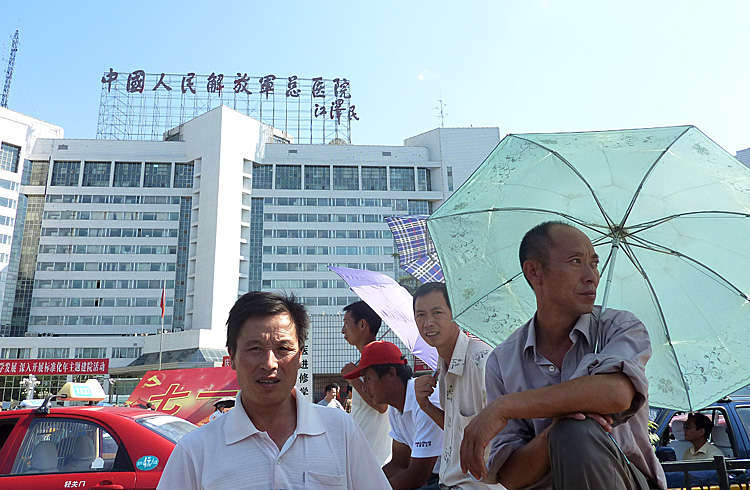 Men stand at the entrance of the 301 Military Hospital in Beijing