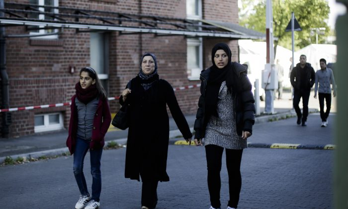 A Syrian refugee family, Reem Habashieh (R), her mother Khawla Kreem (C), sister Raghad Habashieh and the brothers Yaman Habashieh, background right, and Mohammed Habashieh, back ground left, walk from their temporary accommodation facility to go to the central registration center for refugees and asylum seekers LaGeSo in Berlin, Sept. 9, 2015. The family arrived in Berlin around week ago, five of the 37,000 who have flooded into Germany this month seeking a new life. (AP Photo/Markus Schreiber)