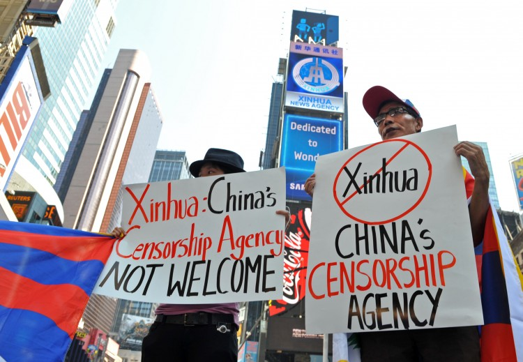Students for a Free Tibet protest below a new electronic billboard leased by Xinhua (2nd from top), on Aug. 1 in New York's Times Square. (Stan Honda/AFP/Getty Images)