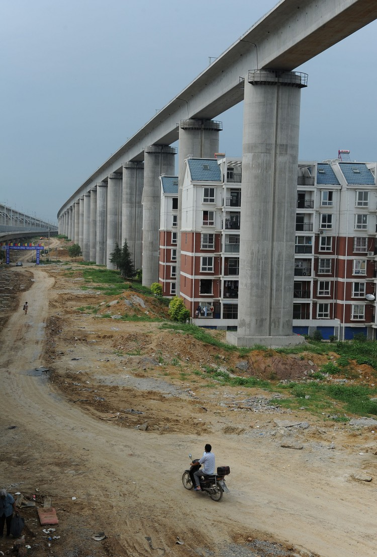 Residential buildings sitting between concrete supports of a high-speed train line in Shuandun county, in Hefei, in east China's Anhui province.  (STR/AFP/Getty Images)