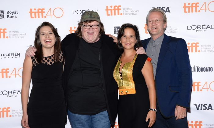 """Director Michael Moore, second from left, poses with people in his film, from left Jenny Tumas, Amel Smaoui and Pasi Sahlberg at the """"Where to Invade Next"""" premiere  on day 1 of the Toronto International Film Festival at The Princess of Wales Theatre on Thursday, Sept. 10, 2015, in Toronto. (Photo by Evan Agostini/Invision/AP)"""