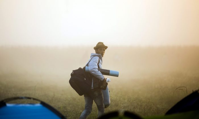 A migrant leaves the camp and walks through a field to avoid checkpoints along the railway tracks connecting Horgos and Szeged near Roszke, Hungary, at the Hungarian-Serbian border, on Sept. 13, 2015. (Balazs Mohai/MTI via AP)