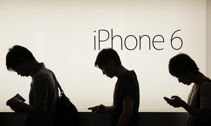 People wait to buy the new Apple iPhone 6 and 6 Plus devices outside an Apple store in Hong Kong on Sept. 19, 2014. (AP Photo/Vincent Yu)