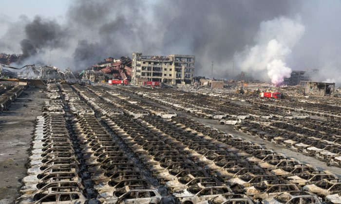 Smoke billows from the site of an explosion that reduced a parking lot filled with new cars to charred remains at a warehouse in northeastern China's Tianjin municipality on Aug. 13, 2015. (AP Photo/Ng Han Guan)