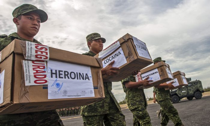 Members of the Mexican Army carry boxes with heroin, cocaine and methamphetamine to be incinerated at a military base in Monterrey, Nuevo Leon state, on August 23, 2013. (Julio Cesar Aguilar/AFP/Getty Images)