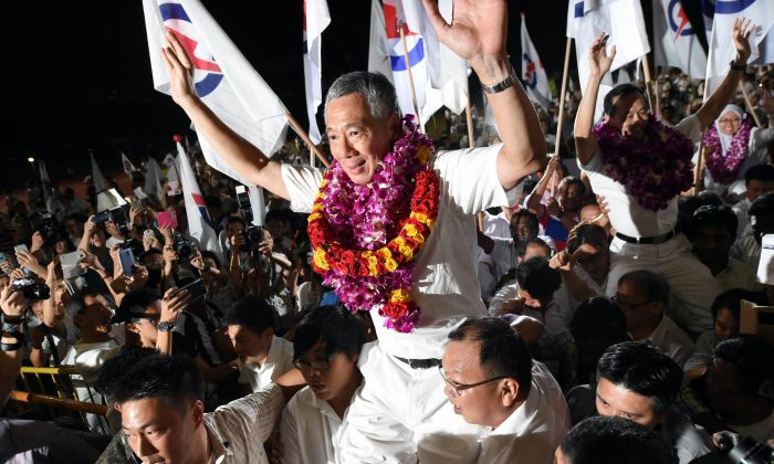Singapore's Prime Minister Lee Hsien Loong, of the People's Action Party celebrates after winning the general election in Singapore on September 12, 2015. Singaporeans voted on September 11 in the most hotly contested election in the country's history after massive turnouts at opposition rallies boosted chances that a two-party system will emerge from half a century of domination by the ruling party. The People's Action Party (PAP), co-founded by the late independence leader Lee Kuan Yew and now led by his son, Prime Minister Lee Hsien Loong, is widely expected to retain a clear majority in the 89-seat parliament.   AFP PHOTO / ROSLAN RAHMAN        (Photo credit should read ROSLAN RAHMAN/AFP/Getty Images)