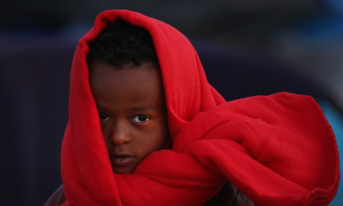 A young boy wraps up to keep warm as migrants wake up to a cold morning at the Hungarian border with Serbia in Roszke, Hungary, on Sept. 13, 2015. A record number of 4,000 people crossed the Hungarian border with Serbia on Sept. 12.  (Christopher Furlong/Getty Images)