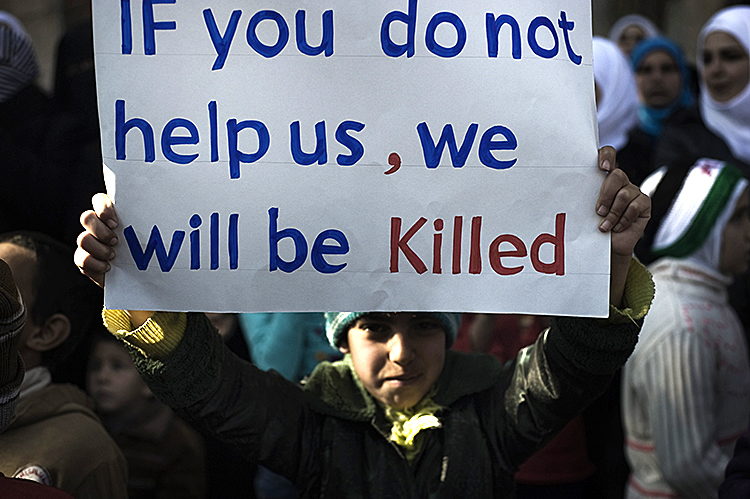 A young boy holds up a sign during an anti-Syrian regime demonstration