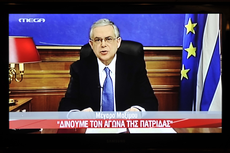 A picture of a TV screen shows Greek Prime Minister Lucas Papademos