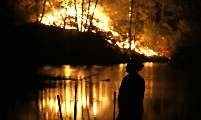 A firefighter stands near a wildfire in Middletown, Calif., on Sept. 13, 2015. (AP Photo/Elaine Thompson)