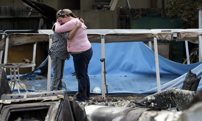 Deanna Hingst, right, embraces her mother Shirley Leuzinger as they stand at the family's destroyed home Monday, Sept. 14, 2015, in Middletown, Calif. (AP Photo/Elaine Thompson)