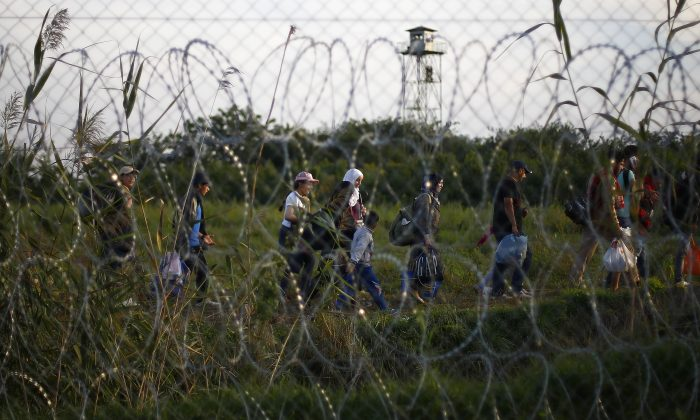 Migrants walk behind a fence after Hungarian police officers close the border line between Serbia and Hungary in Roszke, southern Hungary in Roszke, Monday, Sept. 14, 2015. (AP Photo/Matthias Schrader)