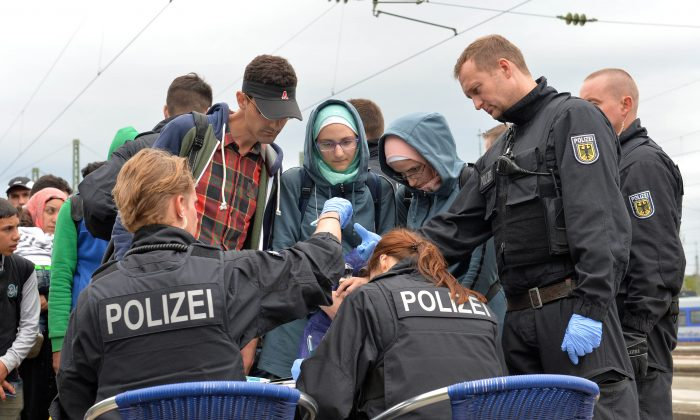 German policemen register refugees at the rail station in Freilassing, southern Germany, Monday, Sept. 14, 2015, before they take them away in busses. (AP Photo/Kerstin Joensson)