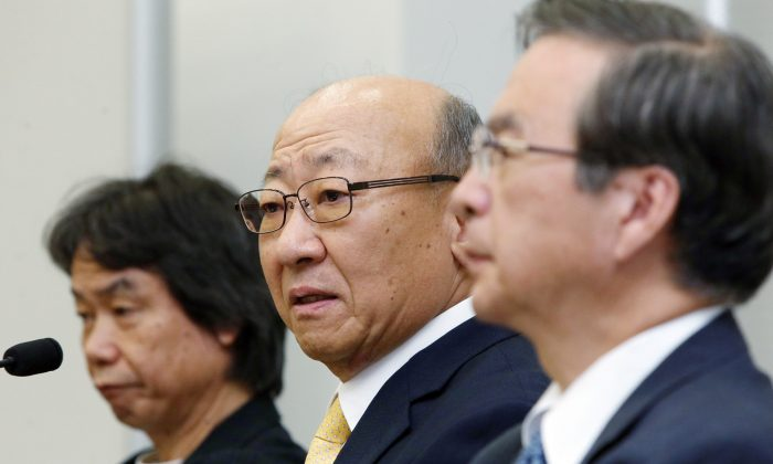 Tatsumi Kimishima (C), newly appointed president of Japanese videogame giant Nintendo speaks to reporters at the Osaka Stock Exchange on Sept. 14, 2015, while Nintendo's famous game creator Shigeru Miyamoto (L) looks on. (Jiji Press/AFP/Getty Images)
