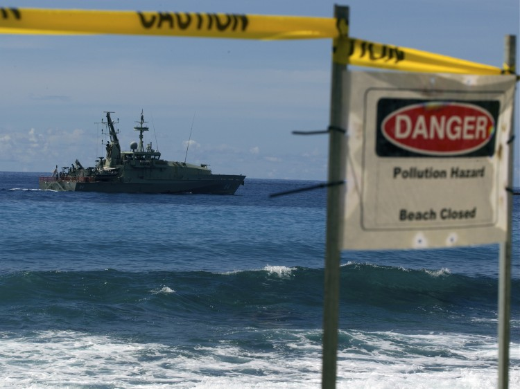 Australian Navy boat cruises by a closed beach