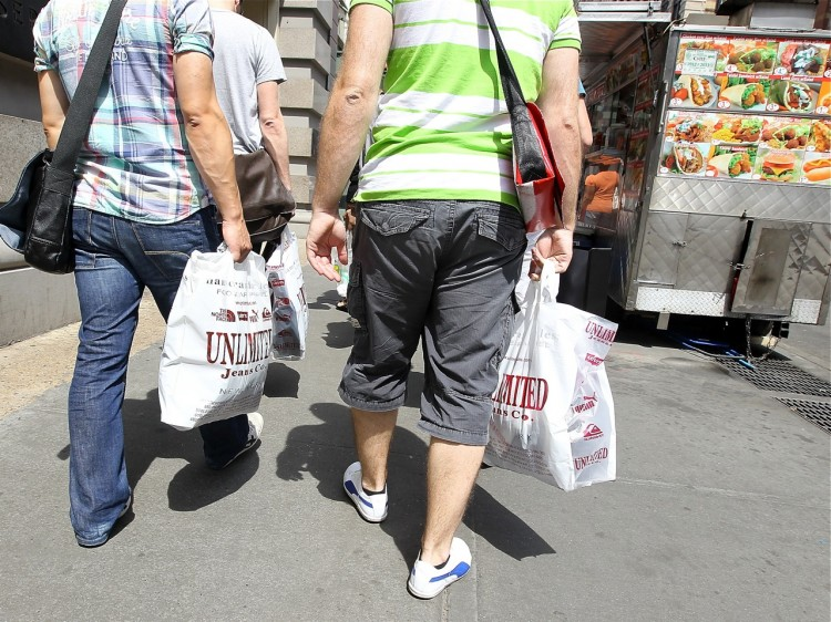 Pedestrians carry shopping bags