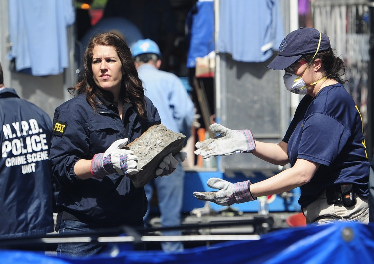 New York police and FBI agents remove pieces of concrete
