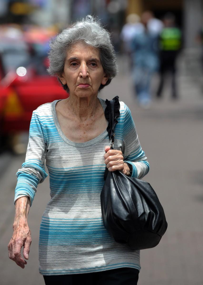 An elderly woman walks in San Jose