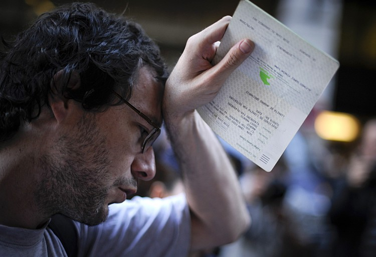 A man holds his savings book on May 14 during a protest held outside Caja Madrid's headquarters in Madrid