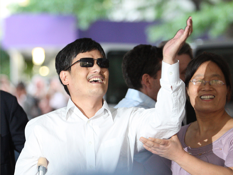 Chen Guangcheng gestures before making remarks to the media