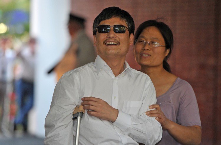 Chinese activist Chen Guangcheng (C) and his wife Yuan Weijing (R) arrive at the New York University Village apartment complex in Manhattan in New York, May 19 Mladen Antonov/AFP/GettyImages)