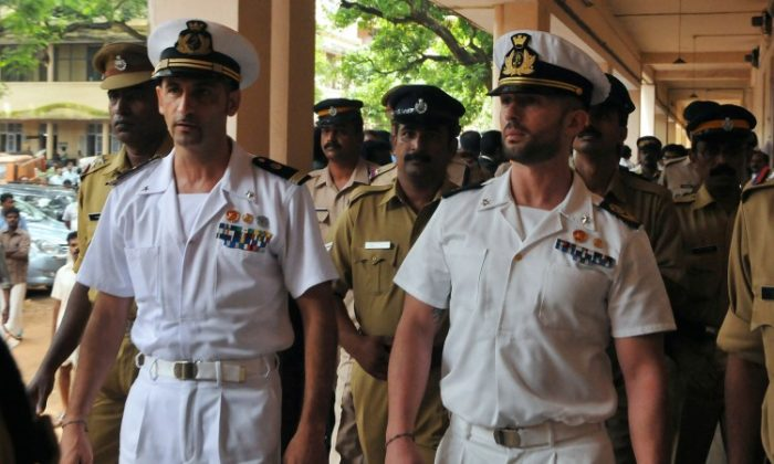 Italian marines Latore Massimiliano (2L) and Salvatore Girone (2R) are escorted by Indian police outside a court in Kerala, India on May 25, 2012. (STRDEL/AFP/GettyImages)