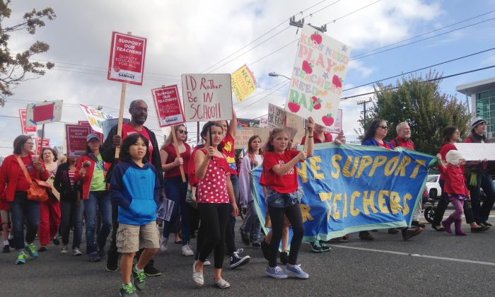 Supporters of striking Seattle teachers take part in a march Tuesday, Sept. 15, 2015, in downtown Seattle. Seattle teachers announced Tuesday that they reached a tentative agreement with the city's school district, but said they're remaining on picket lines pending the deal's approval. (AP Photo/Phuong Le)