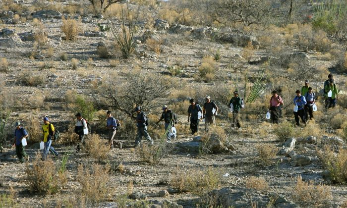 Mexican immigrants walk in line through the Arizona desert near Sasabe, Sonora State, in an attempt to illegally cross the U.S.-Mexico border, on April 6, 2006. (Omar Torres/AFP/Getty Images)