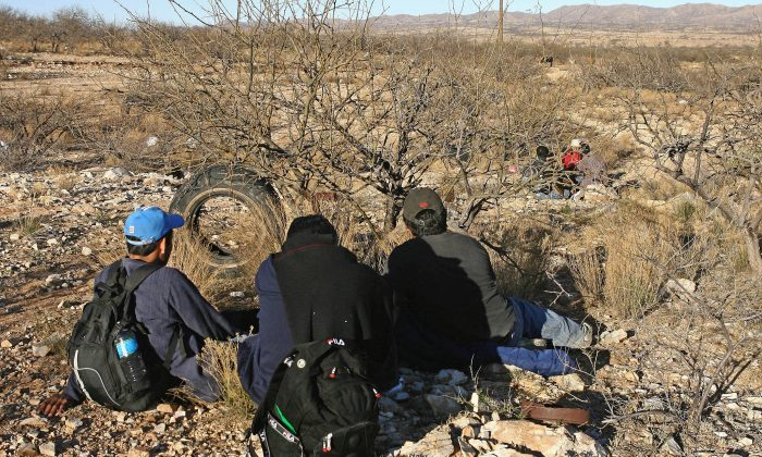 Mexican immigrants take a rest behind bushes in the Arizona Desert near Sasabe, Sonora State, during an attempt to illegally cross the U.S.-Mexico border, on April 6, 2006. (Omar Torres/AFP/Getty Images)