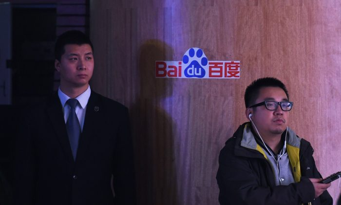 A journalist and security guard stand near a Baidu logo during a press conference at the Baidu headquarters in Beijing on Dec. 17, 2014. (Greg Baker/AFP/Getty Images)