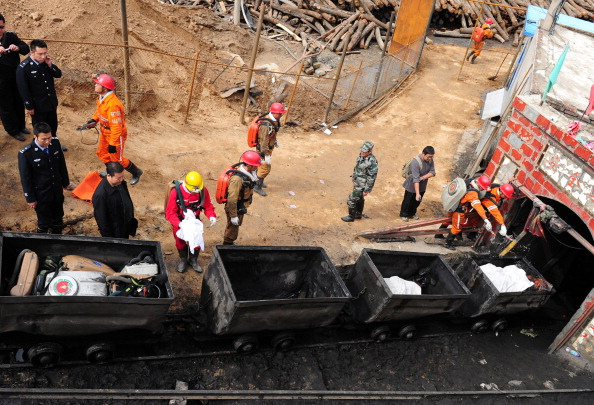 Chinese rescuers remove bodies of miners killed when the cable of a rail carriage taking workers into the mine snapped, sending the 34 miners plummeting into the pit, in Baiyin, located in China's Gansu Province on September 25, 2012.  (STR/AFP/GettyImages)