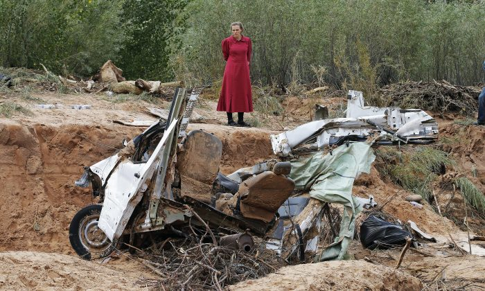 A woman looks at a damaged vehicle swept away during a flash flood Tuesday, Sept. 15, 2015, in Hildale, Utah. The floodwaters swept away vehicles in the Utah-Arizona border town, killing several people. (AP Photo/Rick Bowmer)