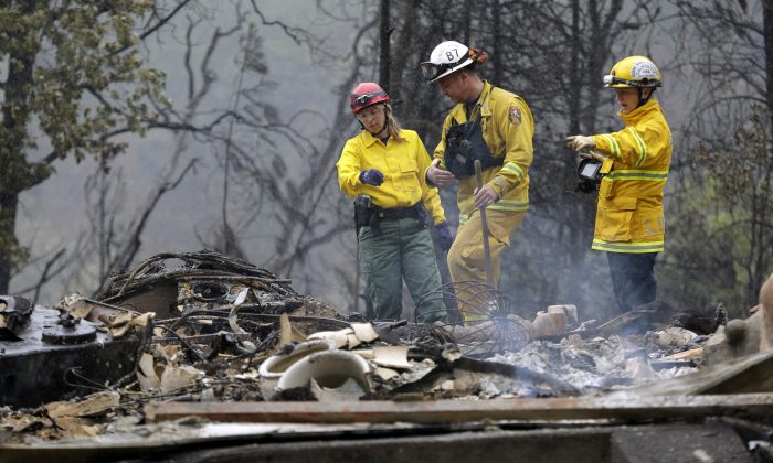 Firefighter Sean Norman, center, and search dog handlers Mary Cablk, left, and Lynne Engelbert look over the remains of a home in the Anderson Springs area, Wed., Sept. 16, 2015, near Middletown, Calif. (AP Photo/Elaine Thompson)