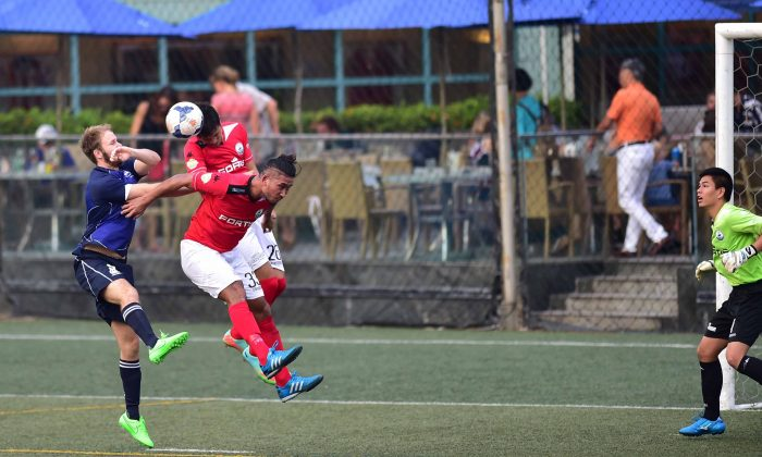 An on target header by Robbie Bacon of HKFC (Blue) gives HKFC their first goal in their 3-1 win over Sun Hei in the HKFA First Division at the HKFC on Sunday Sept 13. (Bill Cox/Epoch Times)