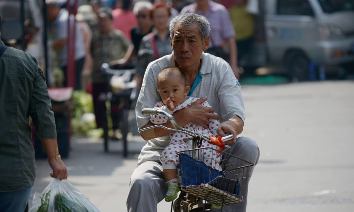 An elderly man holds a baby in his arms as he rides a bicycle along a road in Beijing on September 8, 2015. (WANG ZHAO/AFP/Getty Images)