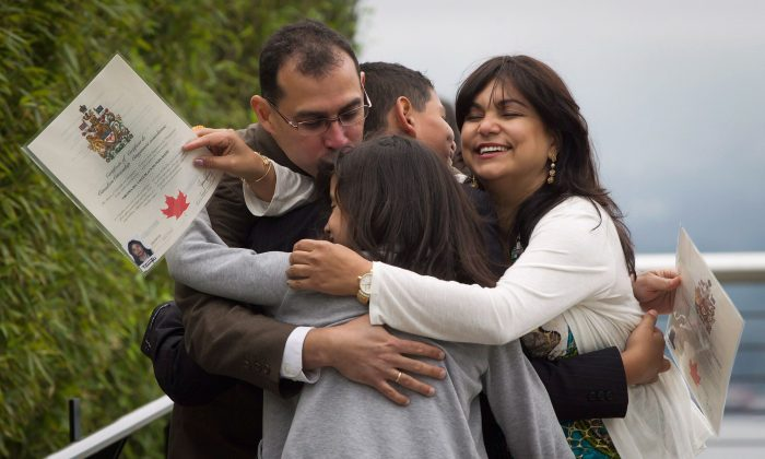 Adrian Pernalete (L) and his family, originally from Venezuela, participate in a group hug after being sworn in as Canadian citizens during a special Canada Day citizenship ceremony in Vancouver on July 1, 2012. A new Statistics Canada report has found that nearly three quarters of university-educated immigrants received their degrees outside the country. (The Canadian Press/Darryl Dyck)