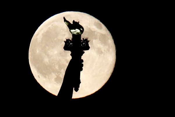 A blue moon rises behind the torch of the Statue of Liberty seen from Liberty State Park in Jersey City, N.J., Friday, July 31, 2015. A blue moon happens when the moon rises in its full stage twice during the same month. (AP Photo/Julio Cortez)