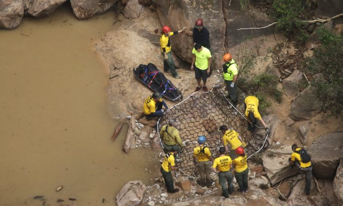 Search and rescue team members place a litter in a net for helicopter transport after finding a body in Pine Creek on Wednesday, Sept. 16, 2015, in Zion National Park, near Springdale, Utah. (AP Photo/Rick Bowmer)