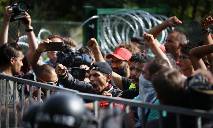 A cameraman and photographers cover a migrant protest against Hungarian police in Horgos, Serbia, on Sept. 16, 2015. (Christopher Furlong/Getty Images)