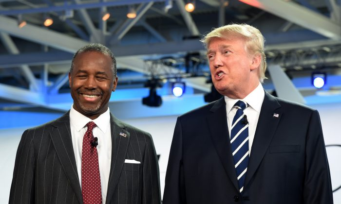 Neurosurgeon Ben Carson (L) smiles as real estate magnate Donald Trump speaks after they arrived on stage for the Republican presidential debate at the Ronald Reagan Presidential Library in Simi Valley, California on Sept. 16, 2015. (Robyn Beck/AFP/Getty Images)